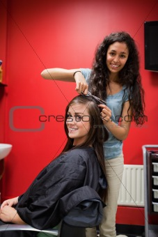 Portrait of a happy hairdresser cutting hair
