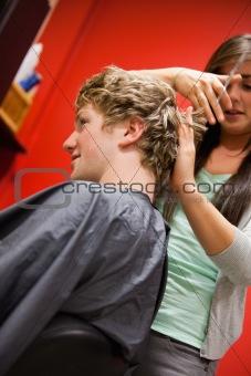 Portrait of a serious woman cutting a man's hair