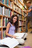 Portrait of a student with a book while her classmate is choosing a book