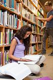 Portrait of a student reading a book while her classmate is choosing a book