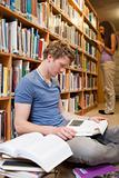 Portrait of a male student reading books while his classmate is reading