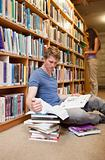 Portrait of a male student making research while his classmate is reading