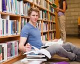 Male student doing research while his classmate is reading