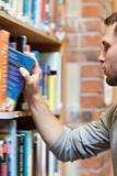 Portrait of a male student picking a book
