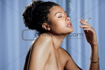 Beautiful sensual and naked woman enjoying a cigarette