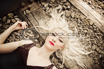 Beautiful young girl lying on rails, closeup portrait