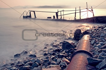 old metal pipe and road to sea