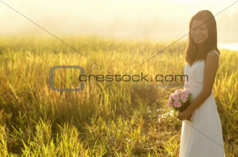 Asian bride at outdoor in a morning surrounding by golden sunlig