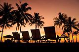 Row deckchairs on beach at sunset,