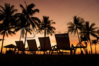 Row deckchairs on beach at sunset,