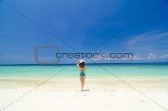 asian girl walking towards sea