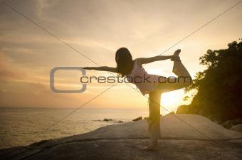 yoga girl performing yoga pose on a beach