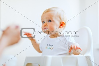 Eat smeared lovely baby in baby chair feeding by mother
