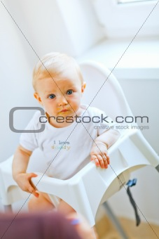 Eat smeared adorable baby in baby chair interestedly looking
