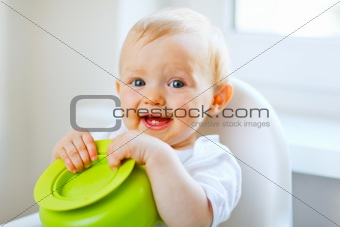 Adorable baby girl sitting in baby chair and playing with plate