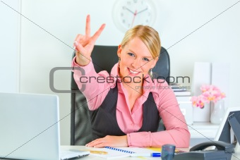 Smiling business woman sitting at office desk and  showing victory gesture