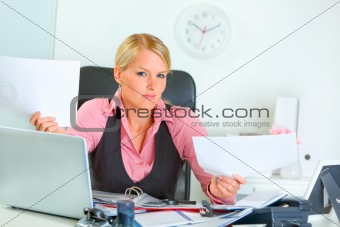 Confused business woman at office desk