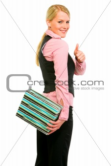 Smiling business woman hiding gift and showing thumbs up