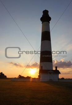 Bodie Island lighthouse silhouetted at sunrise vertical
