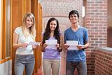 Smiling students holding a piece of paper