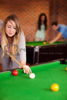 Portrait of a cute woman playing snooker