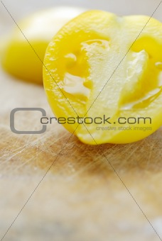 One sliced yellow tomato on chopping board.