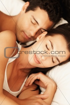 Attractive couple sleeping in bed