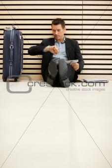 Male entrepreneur checking the time for flight