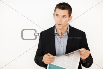 Confident young business man looking away with newspaper