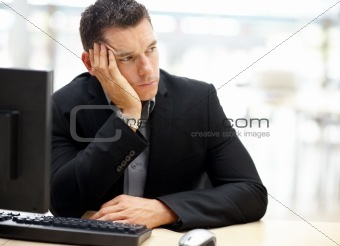Unhappy young business man looking away