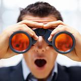 Shocked young male entrepreneur looking through binoculars