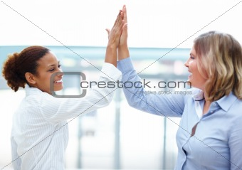 Pretty female business associates giving eachother a high five