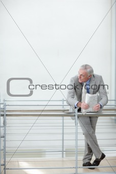 Senior businessman leaning on railing and looking at copyspace