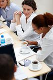 Pretty young woman having coffee in office meeting