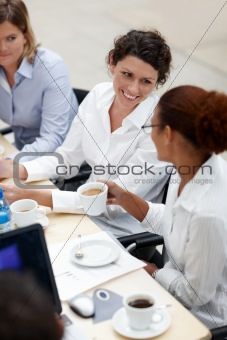 Happy young woman having coffee in office meeting
