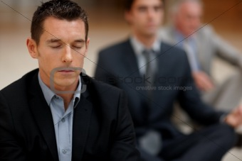 Young business man meditating with colleagues at the back