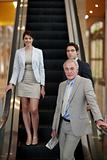 Business associates standing on escalator