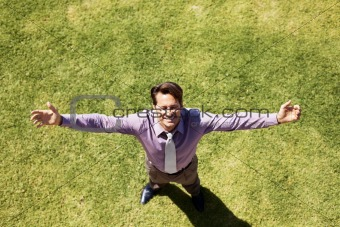 Businessman standing with arms wide open on grass