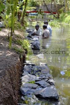 Three men underwater dry stone walling Kerala India