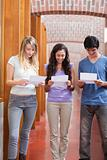 Portrait of students reading a piece of paper