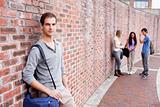 Student leaning on a wall while his friends are talking