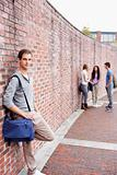 Portrait of a student leaning on a wall while his friends are talking