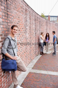 Portrait of a male student leaning on a wall while his friends are talking