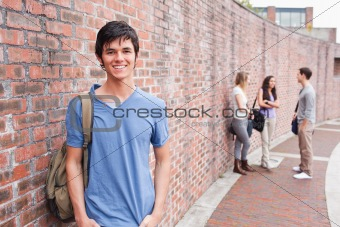 Male student posing while his friends are talking
