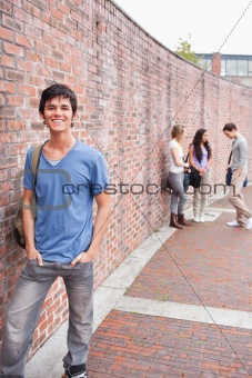 Portrait of a student posing while his friends are talking