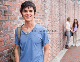 Handsome student posing while his friends are talking