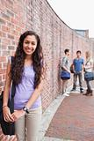 Portrait of a smiling student posing while her friends are talking