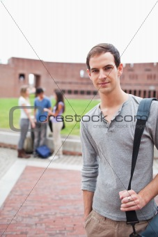 Portrait of a student posing while his classmates are talking