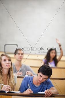 Portrait of students taking notes while their classmate is raising her hand