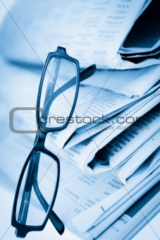 Newspapers and black glasses